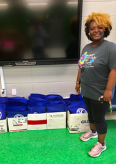 Lincoln Elementary principal LaDonna Braswell stands with a number of backpacks that will be available for second-graders at her school for the summer.