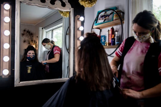 Cayley Sipes straightens Morgan Taylor's hair at Bombshell Studio in Jackson, Tenn., Monday, May 4, 2020. Sipes and Taylor wear face masks in a room alone together when Sipes colored and cut her hair.