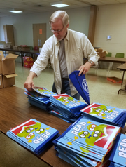Retired teacher, administrator and coach Bob Lay helps sort books for backpacks for the ARISE2Read program.