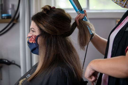 Morgan Taylor gets her hair straighten by Stylist Cayley Sipes at Bombshell Studio in Jackson, Tenn., Monday, May 4, 2020. Sipes and Taylor wear face masks in a room alone together when Sipes colored and cut her hair. Bombshell is ensuring everyone's safety by setting regulations and continuing to sanitize.