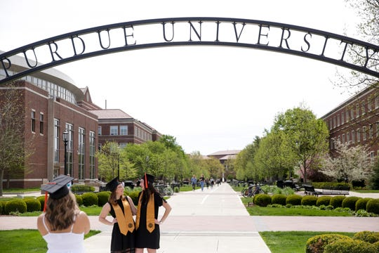 Kassie Zamora, left, takes a photo of Lauren Novak, center, and Staphanie Godoshian, right, as they pose for graduation photos by the Centennial Arch at Purdue University, Monday, May 4, 2020 in West Lafayette.