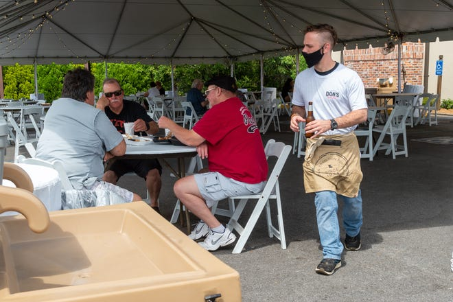 Server Hunter Richard serving customers outdoors under tent in parking lot at Don's Seafood. Monday, May 4, 2020.