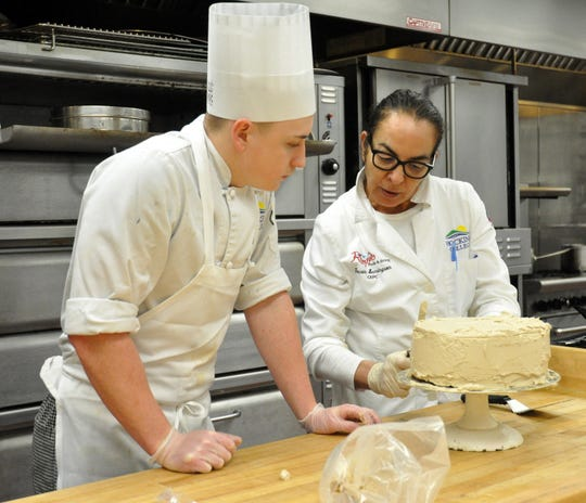 In this photograph from Feb. 2020, Chef Touria Semingson helps a student during a baking lab at Hocking College in Nelsonville, Ohio. Semingson and other instructors at the school had to adapt quickly when the school suspended in-person classes in March due to the coronavirus pandemic.