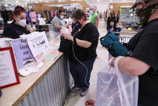 Customer Pam Byrne checks out at a Peddlers Mall register as fiance Josh Carpenter holds her oxygen tank after the two went shopping Monday afternoon at the Clarksville store.