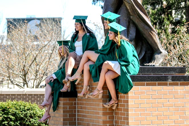 From left, senior roommates Teagan Leyanna, Olivia Woods, Kiera Hamada and Lauren Umbarger pose for a picture at the Sparty statue on Friday, May 1, 2020, on the MSU campus in East Lansing.