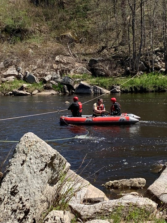 Personnel from the Clark County Sheriff's Office and other agencies search the Black River for a missing man Sunday, May 3, 2020, a day after the boat he was in capsized.