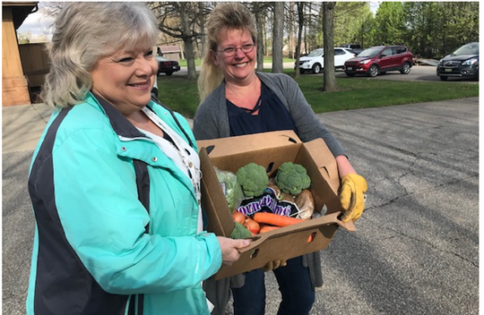 Pam Drake, executive director of the Independent Living Center of North Central Ohio, left, and agency employee Wendy Byerly carry some food and produce distributed to 300 clients Monday outside the office on Village Mall Drive in Ontario.