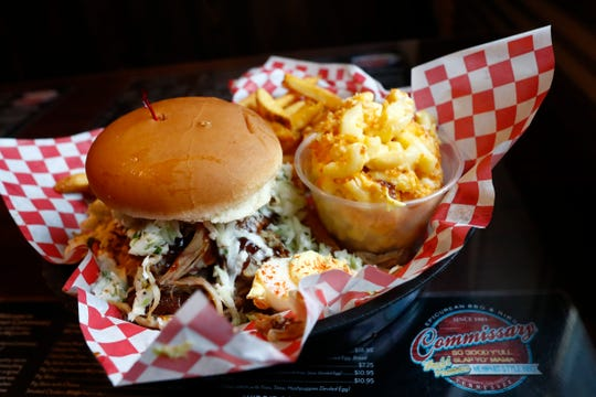A pulled pork sandwich with slaw, french fries and mac and cheese at the Collierville Commissary BBQ on their first day of reopening dine-in service for customers on Monday, May 4, 2020.