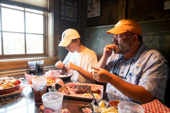 George Hudspeth and his son Charlie eat a rack of ribs at the Collierville Commissary BBQ on their first day of reopening dine-in service for customers on Monday, May 4, 2020.