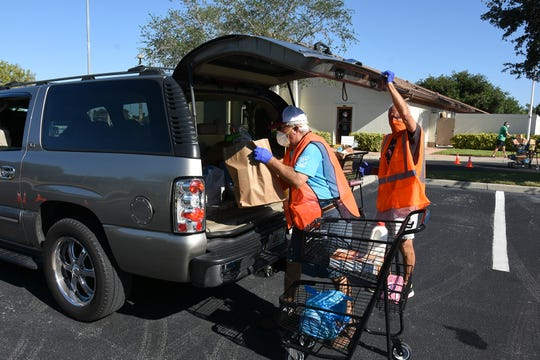 Volunteer James Cuevas loads groceries into the truck of Jesus Marti. Our Daily Bread food pantry fed 622 families on Marco Island last week, providing each with at least 45-50 lbs. of a variety of grocery items.