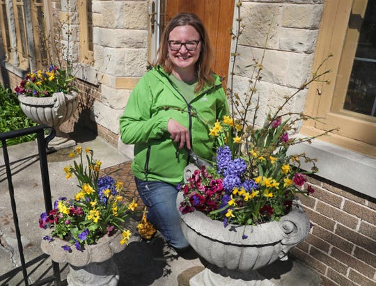 Kristyn Greenfield shows the planters at her Wauwatosa home. Large planters can complement the architecture of the house.
