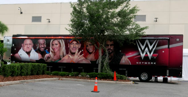 A trailer set up near a satellite truck to transmit wrestling broadcasts is parked outside the WWE Performance Center Tuesday, April 14, 2020, in Orlando, Fla. Florida's top emergency official last week amended Gov. Ron DeSantis' stay-at-home order to include employees at the professional sports and media production with a national audience, if the location is closed to the public.