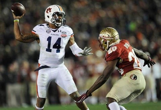 Auburn quarterback Nick Marshall (14) gets a pass away while defended by Florida State defenscive back Lamarcus Joyner (20) in second half action of the BCS National Championship Game on Monday January 6, 2014 in Pasadena, Ca.