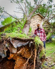 Kelvin Rankins stands near a tree that was uprooted in the yard of his home on Barfield Crescent Road during a storm on Sunday, May 3, 2020.