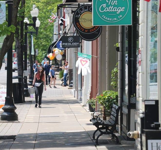 Passersby walk on Main Street on May 4, 2020.