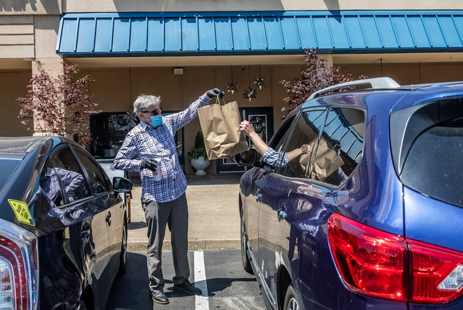Jim Hagy, owner of Chef's Market in Goodlettsville, delivers curbside pickup orders from his restaurant Monday, May 4, 2020.