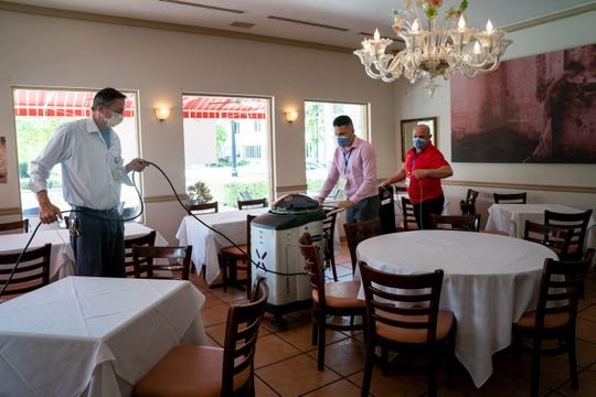 From left to right, Matt Cottage, maintenance supervisor at NCH, Alex Cruz, operations manager at NCH, and Carlos Marrero, area director at NCH, set up a Xenex LightStrike Germ-Zapping robot, which uses pulsed xenon ultraviolet light to disinfect rooms, at Bellini on Fifth Italian Ristorante in Naples on Monday, May 4, 2020. NCH is using the robots to disinfect seven different Naples restaurants this week as a thank you for the meals they donated to NCH staff during the pandemic.