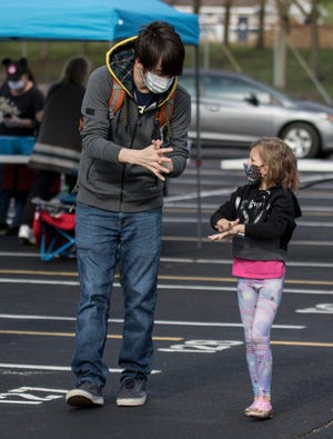 A father shows his daughter how to wash her hands and rub-in all the hand sanitizer they were provided at the entrance of a recent Saturday Granville Farmers Market event.