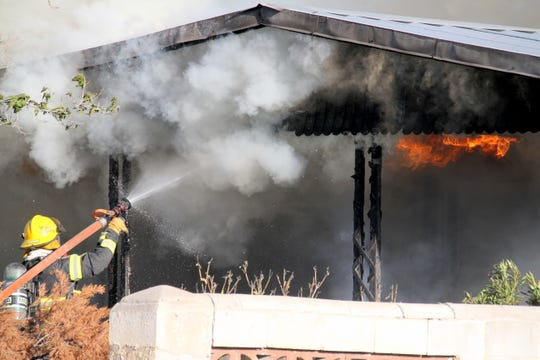 Deming firefighters battled hot spots along the abandoned trailer and also 90-degree temperature on Sunday.