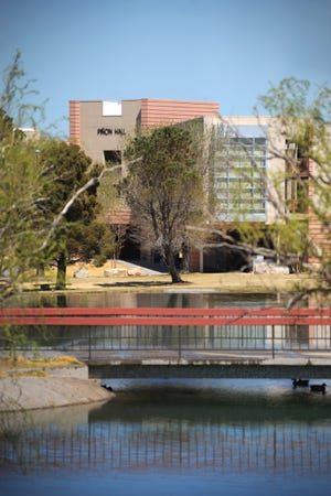 An exterior view of Pinon Hall with the duck pond appearing in foreground.