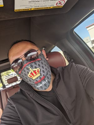 Fernando Corona wears a Corona's Plastering face mask. His company is giving 300 of the face masks free to the community on Saturday.