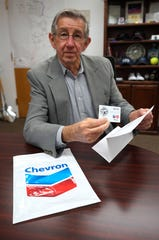 Mayor Dale Janway hold a fuel gift card donated by Chevron.