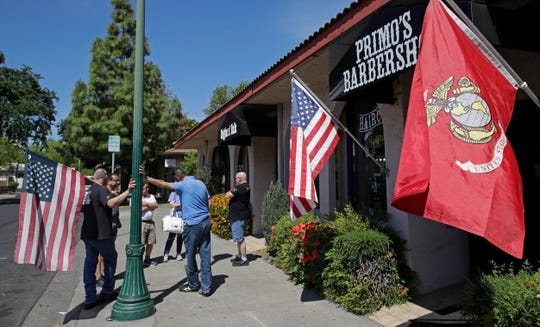 People wait in line to have their hair cut at Primo's barbershop on Monday, May 4, 2020, in Vacaville, Calif. Juan Desmarais, a former US Marine, re-opened his business on Friday, May 1, 2020, after realizing it could be months before he had permission to operate due to COVID-19 restrictions. (AP Photo/Ben Margot)