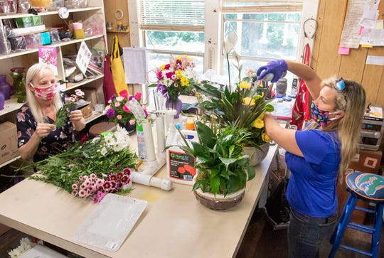 A Flower Shop co-owners Keri Hankins, left, and Dannielle Price create a fresh flower arrangements on Monday.
