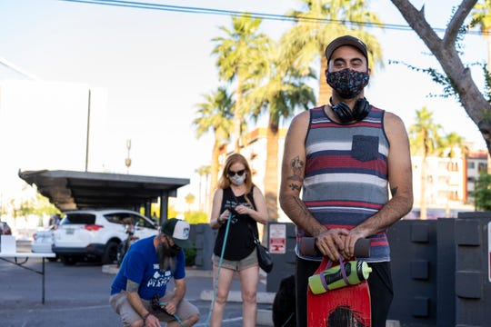 Brian Kearley waits in line to get food at Hood Burger outside Cobra Arcade Bar in downtown Phoenix on May 2, 2020. Hood Burger, a nonprofit pop-up eatery, is offering food to help the Arizona Coalition to Arizona Coalition to End Sexual & Domestic Violence.