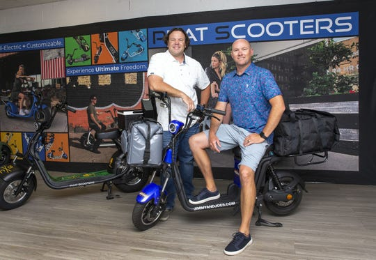 Beau Ralphs and Peter Johnson (right) owners of Phat Scooters on a Phleet Food Delivery eBike at their showroom in Tempe. During the coronavirus pandemic Phat Scooters donated a dozen scooters to local restaurants to use for delivery services.