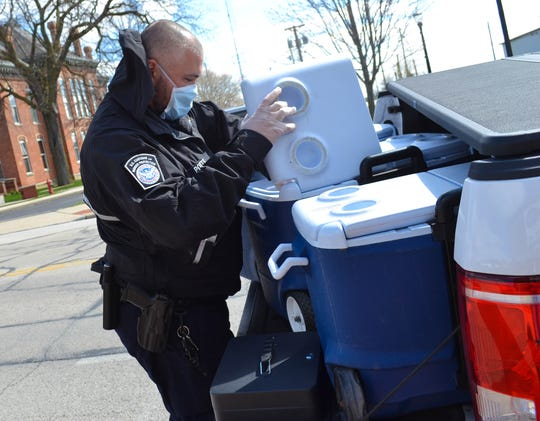 CBP officer Brian Potts retrieves a lunch out of the cooler on the back of the U.S. Customs and Border Protection truck. Potts was assisting with the Grab and Go lunch program for seniors.