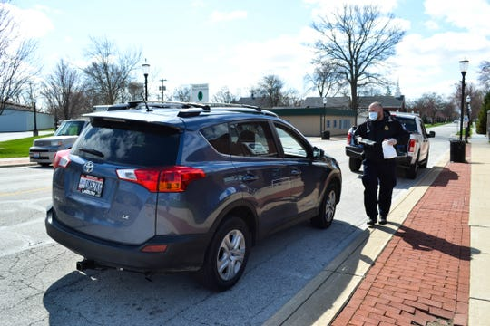 U.S. Customs and Border Protection officer Brian Potts approaches a car during a recent Grab and Go lunch program for seniors in Genoa.