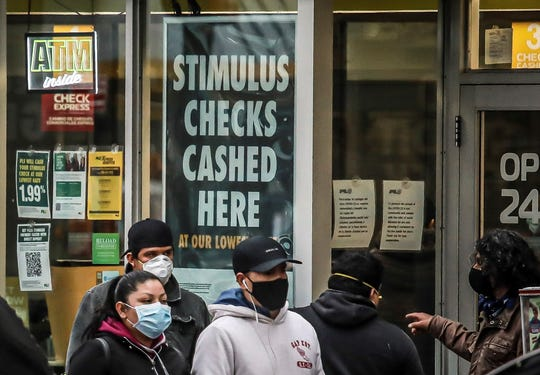 In this April 24, 2020, photo, people wearing face masks due to COVID-19 concerns gather outside a check cashing service center in the Brooklyn borough of New York. (AP Photo/Bebeto Matthews)