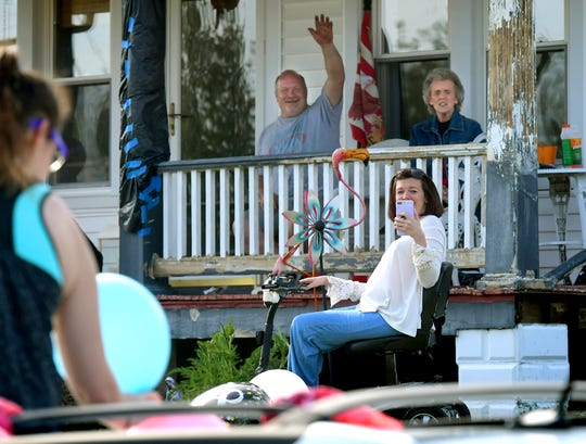 Megan Eagan's mother Cathy Eagan, front, records a drive-by birthday party outside the family's home Saturday, May 2, 2020. Megan's father, Greg, and grandmother Joyce Greenfield sit on the porch. Megan celebrated her 18th birthday Saturday. Bill Kalina photo