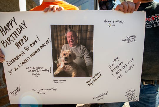 Employees hold up a signed birthday card for Herb Baker while singing Happy Birthday in front of Saubel's in Shrewsbury.