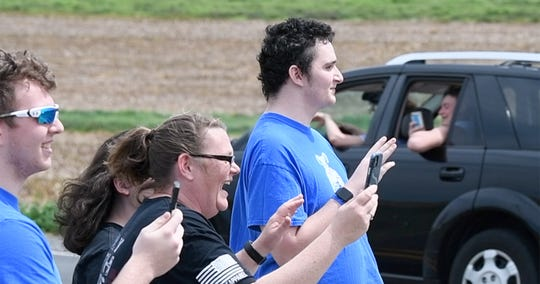 From the left, friend Gabe Hulslander, mother Jennifer Maloney and Patrick Maloney wave to well-wishers as they pass his East Hopewell Township home to celebrate Maloney's 18th birthday.