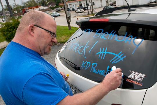 Kennard-Dale powerlifting head coach Niko Hulslander writes Happy Birthday on the back of his SUV before leading the drive-by birthday caravan past Patrick Maloney's home.