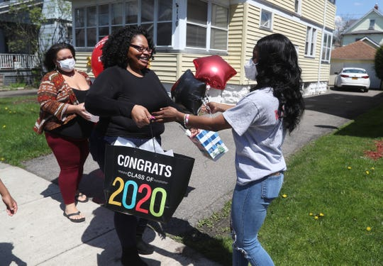 Sierra Burrows, a graduating senior at Wilson Magnet, is greeted by family friend Sedawnie Williams and Tyshauna Clark (left).  Williams joined a Facebook Group of Senior Fairies who choose a graduating high school senior to celebrate them during the Coronavirus pandemic.