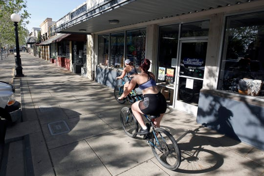 A pair of bicyclists ride past closed businesses on Plumas Street in Yuba City, Calif., Monday, April 27, 2020, during the coronavirus outbreak. Representatives of Sutter County, where Yuba City is located, joined five other counties calling on Gov. Gavin Newsom to allow them to exercise local authority to implement a careful and phased reopening of the local economies. (AP Photo/Rich Pedroncelli)