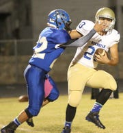 Rochelle's Jacob Cox attempts to avoid a tackle by Eden's Dante Torres during a game in 2014.