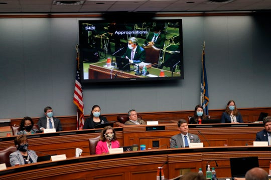 Members of the Louisiana House Appropriations Committee, some wearing masks and others not, listen to testimony by state commissioner of administration Jay Dardenne, seen on screen above, in Baton Rouge, La., Monday, May 4, 2020.