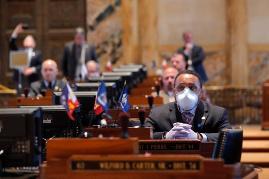 In this March 31, 2020, file photo, State Rep. Vincent Pierre, D-Dist. 44, wears a mask and gloves as legislators convene in a limited number while exercising social distancing due to the new coronavirus pandemic at the state Capitol in Baton Rouge, La. Louisiana lawmakers are restarting their legislative session Monday, May 4, 2020, in a state reshaped by COVID-19.