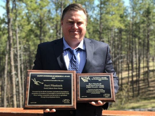 South Dakota News Watch Content Director Bart Pfankuch holds two plaques awarded for agricultural coverage in 2019, including one for being named the national Agricultural Journalist of the Year.
