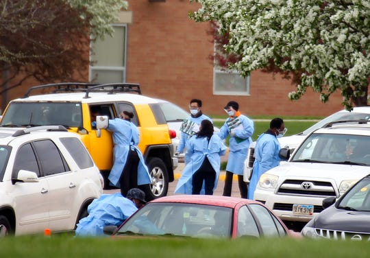 Healthcare workers get patient information from cars in line at a coronavirus testing site for Smithfield employees in the Washington High School parking lot on Monday, May 4, in Sioux Falls.