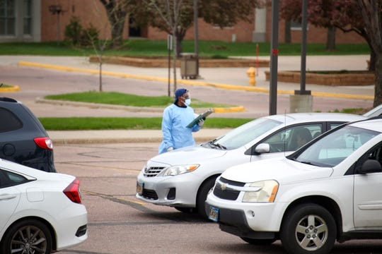 A worker get patient information from people waiting in line for coronavirus testing site in the Washington High School parking lot on Monday, May 4, in Sioux Falls.