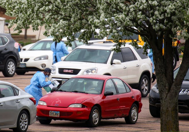 Workers get patient information from people waiting in line for coronavirus testing site in the Washington High School parking lot on Monday, May 4, in Sioux Falls.