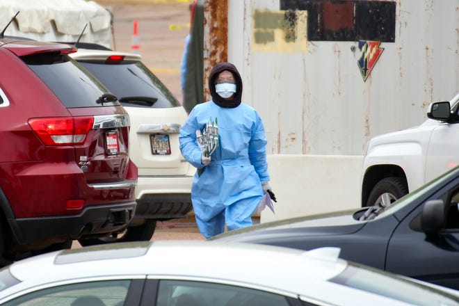 A healthcare worker walks through a sea of cars at a coronavirus testing site in the Washington High School parking lot on Monday, May 4, in Sioux Falls.