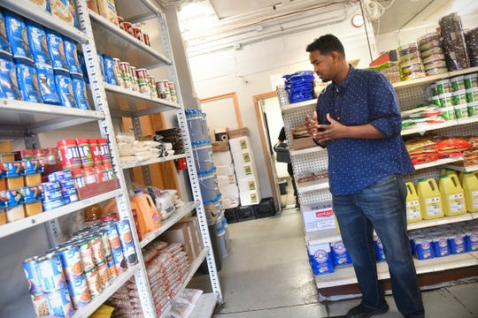 Noor Yussuf  stands next to packages of halal food available for those in need  Monday, May 4, 2020, at Midnimo Grocery & Halal Meat in St. Cloud.