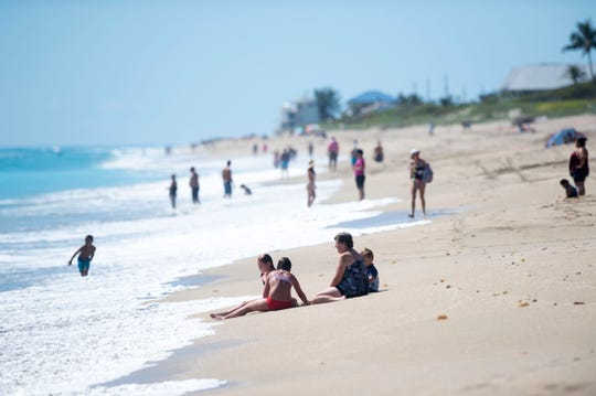 The Jones family (from left) Jordan Jones, 10, Taylor Jones, 13, Patty Jones and Matthew Jones, 5, all of Jensen Beach, were among an estimated 1,000 people who spread out on Stuart Beach on the first day beachgoers were able to access Martin County beaches on Monday, May 4, 2020 on Hutchinson Island. Martin County commissioners voted to reopen the beaches, excluding Hobe Sound Beach and Bathtub Reef Beach, but said they need to follow the CDC's guidelines for social distancing, including staying 6 feet apart from strangers.