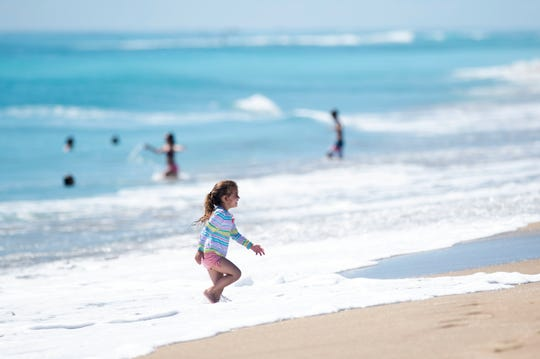 Penelope Kite, 4, of Jupiter, enjoys playing in the ocean as an estimated 1,000 people spread out on Stuart Beach on the first day residents were able to access Martin County beaches on Monday, May 4, 2020, on Hutchinson Island. Martin County commissioners voted to reopen the beaches, excluding Hobe Sound Beach and Bathtub Reef Beach, but said they need to follow the CDC's guidelines for social distancing, including staying six feet apart from strangers.